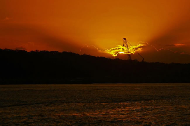 WOW! Spectacular sunrise lights up a construction crane. Gladstone Harbour, Queensland, Australia