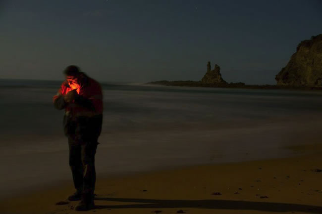 Man lighting up on the beach, near Wonthaggi, Victoria, Australia