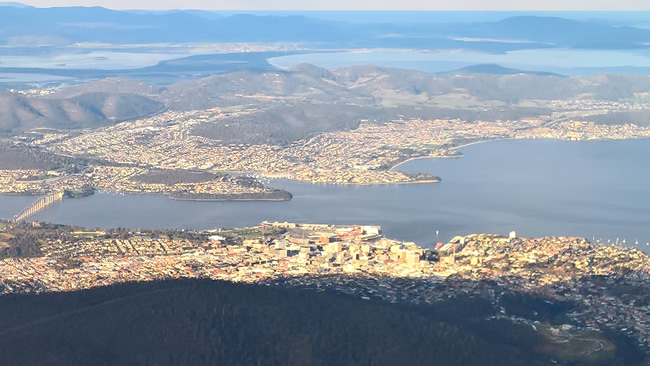 The evening sun slots between the clouds to light up Hobart, from Mt Wellington, Tasmania, Australia